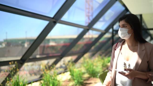 vídeos de stock, filmes e b-roll de jovem viajante mulher olhando através da janela e usando telefone no aeroporto - usando máscara facial - travel destinations