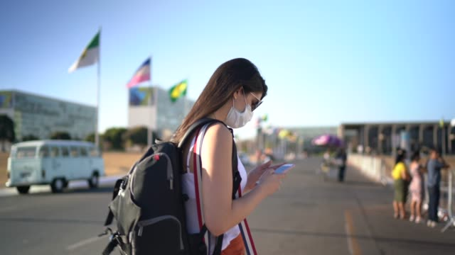 vídeos de stock e filmes b-roll de young traveller woman walking and using mobile phone in brazil - wearing face mask - mochila saco