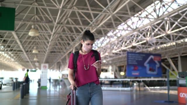 vídeos de stock, filmes e b-roll de jovem viajante andando e usando telefone no aeroporto - usando máscara facial - turista