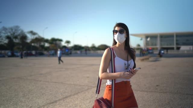 vídeos de stock, filmes e b-roll de jovem viajante andando no brasil - usando máscara facial - turista