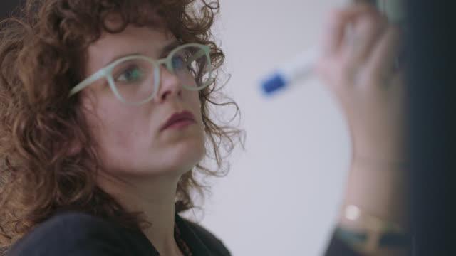 vídeos y material grabado en eventos de stock de cu young trendy businesswoman writes on office whiteboard - determinación