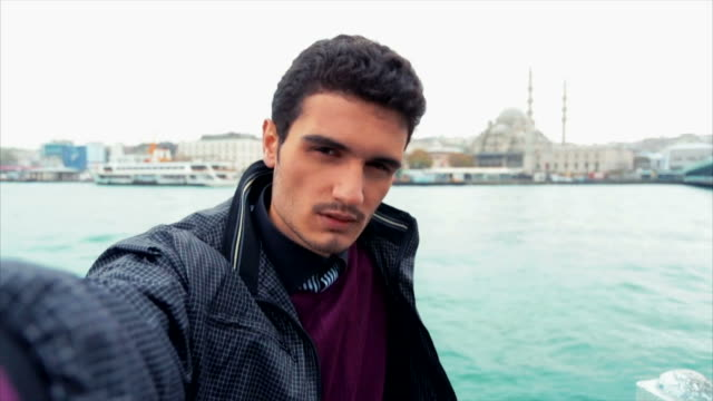 young turkish man taking selfies near galata bridge - yeni cami mosque stock videos and b-roll footage