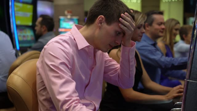 young unhappy man stressed loosing money on slot machine at the casino - loss stock videos & royalty-free footage