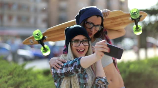vídeos y material grabado en eventos de stock de joven urbano mejores amigos tomando un autorretrato en la ciudad - patinaje en tabla larga