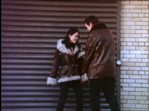 young urban generation x couple in winter coats play fighting in front of building - x世代点の映像素材/bロール