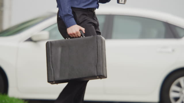 young urban professional businessman crosses a busy city street carrying morning coffee and a briefcase. - parking stock videos and b-roll footage