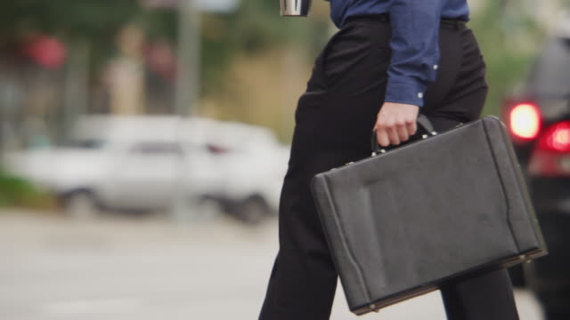 young urban professional businessman crosses a busy city street carrying morning coffee and a briefcase. - aktentasche stock-videos und b-roll-filmmaterial