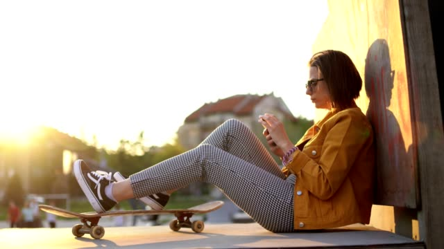 young urban woman using mobile at a skate park at sunset - skateboard park stock videos & royalty-free footage