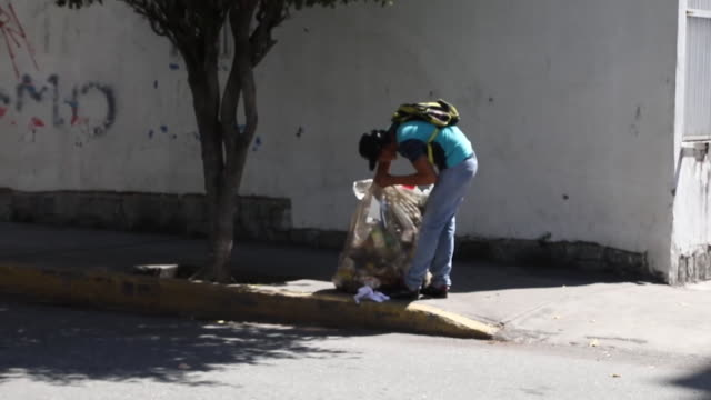 vidéos et rushes de young venezuelan man searching through rubbish for food in caracas - se nourrir des restes