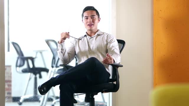 オフィスチェアで話す若いベトナム人ビジネスマン - 座る点の映像素材/bロール