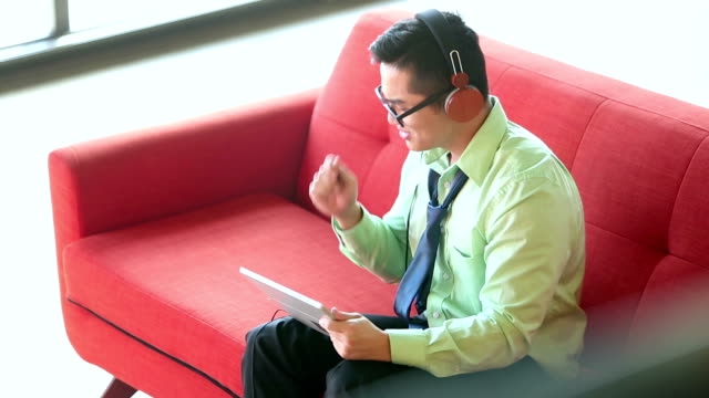 Young Vietnamese businessman listening to music