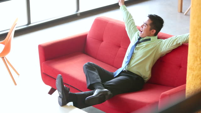 Young Vietnamese businessman relaxing on sofa
