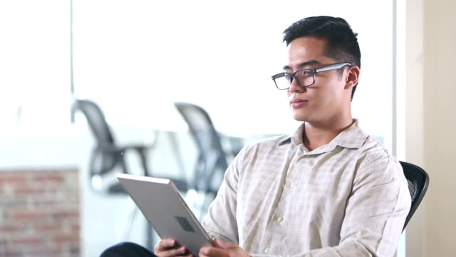Young Vietnamese businessman using digital tablet