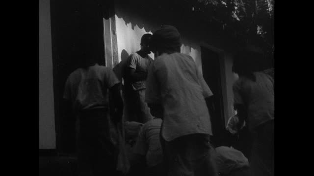 stockvideo's en b-roll-footage met montage young villagers racing across field, stripping off their clothing, and learning a dance from dancing master, using unhewn log as ballet barre / sri lanka - sri lankaanse cultuur