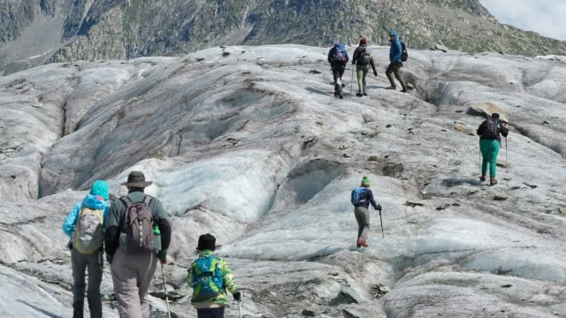 young visitors embark on a guided glacier tour at an exposed portion of the aletsch glacier on august 22 2019 near bettmeralp switzerland at over... - european alps stock videos & royalty-free footage