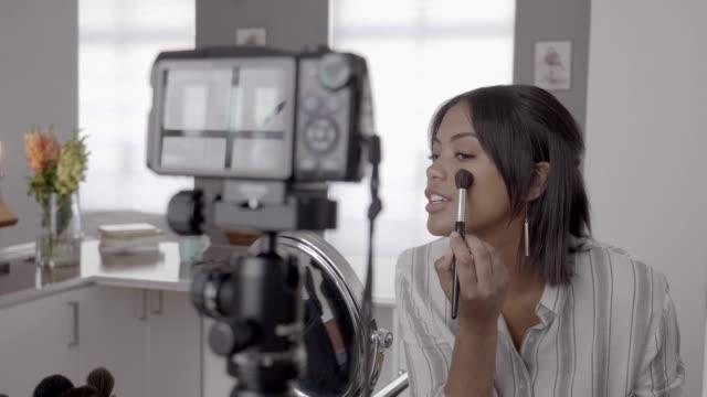 vídeos de stock, filmes e b-roll de young vlogger applying blush while making video on phone - blush
