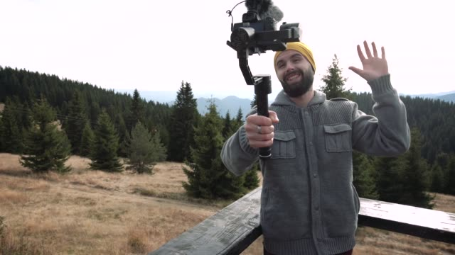 young vlogger making a video in the mountains - side hustle stock videos & royalty-free footage