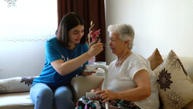 young volunteer feeding aged woman in  home - community care stock videos & royalty-free footage