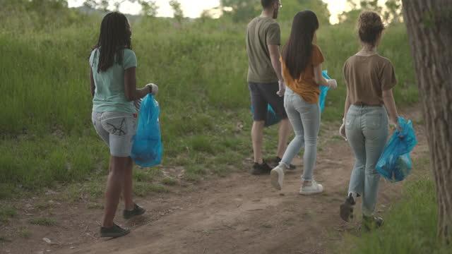 森からゴミを集める若いボランティア - ゴミ袋点の映像素材/bロール