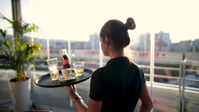 stockvideo's en b-roll-footage met jonge serveerster serveert drankjes in het prachtige café op het dak tijdens de zonnige dag - carrying