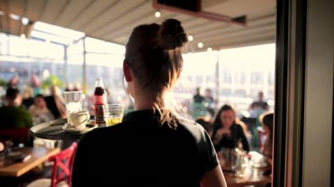 vídeos y material grabado en eventos de stock de joven camarera sirviendo bebidas en la hermosa cafetería de la azotea durante el día soleado - tejado