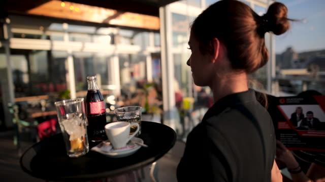 晴れた日に美しい屋上カフェでドリンクを提供する若いウェイトレス - ウェイトレス点の映像素材/bロール