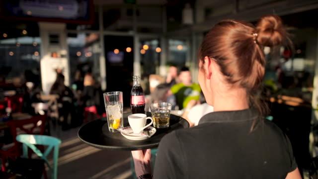 vídeos de stock e filmes b-roll de young waitress serving drinks at beautiful rooftop cafe during sunny day - empregada de mesa