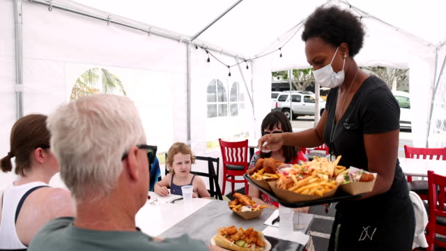 young waitress serving food to customers in outdoor tent wearing a mask - dining stock videos & royalty-free footage