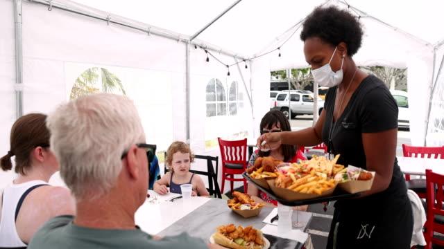 マスクを着用した屋外テントで顧客に食べ物を提供する若いウェイトレス - 食事する点の映像素材/bロール