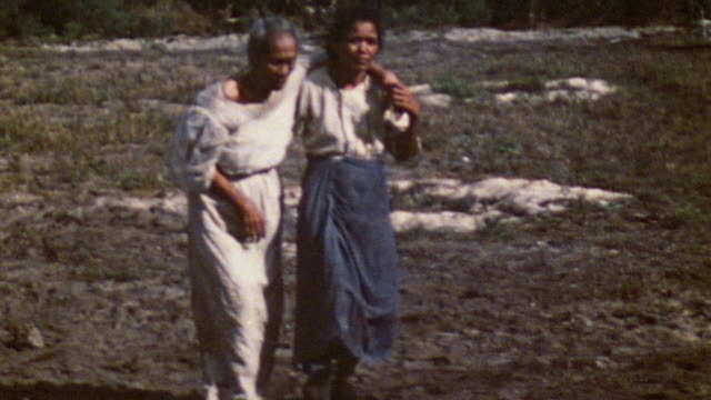 young war victim supports elderly war victim in hobbling walk to join group of displaced civilians / saipan mariana islands - mariana islands stock videos and b-roll footage