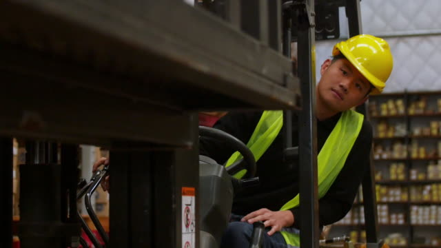 Young warehouse worker operating forklift