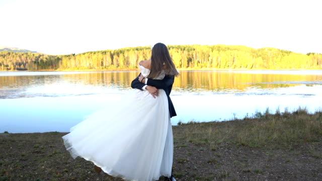 vídeos de stock, filmes e b-roll de casal de casamento jovem tem romance ao pôr do sol - bride