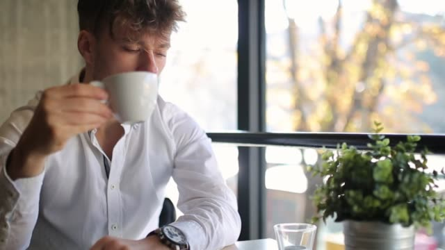 young, well dressed, drinking coffee and answering a phone call, while sitting in coffee bar - solo un uomo giovane video stock e b–roll