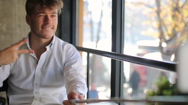 若いよく服を着た男は、コーヒーバーに座って、自分撮りスティックで自分撮りを取って - 死傷者点の映像素材/bロール