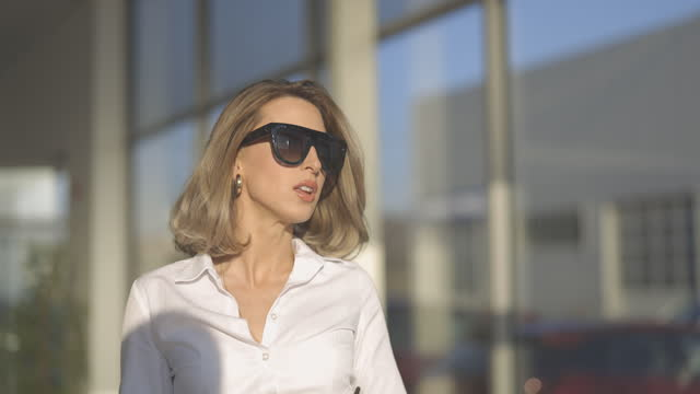 young well dressed woman leaving office building - sunglasses stock videos & royalty-free footage