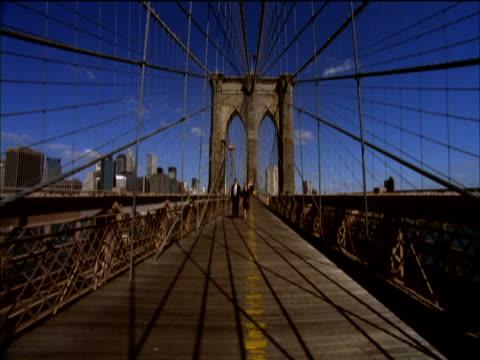 stockvideo's en b-roll-footage met young well-dressed couple walking over brooklyn bridge, new york, usa - zij aan zij
