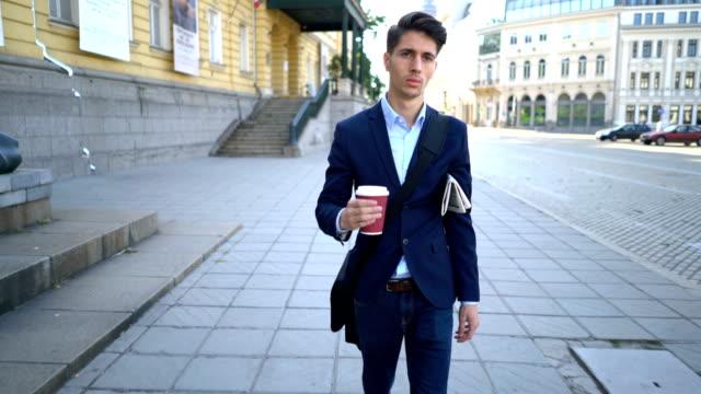Junger gut gekleideter Mann auf der Straße mit Kaffee und Zeitung