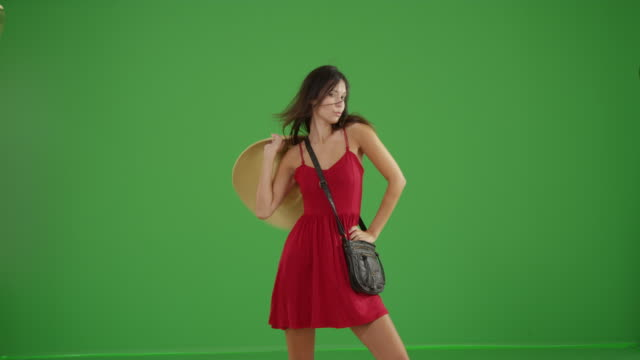 young white girl dances in a red sun dress and floppy hat on green screen - kleid stock-videos und b-roll-filmmaterial