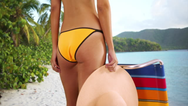 young white girl in yellow swimsuit standing next to a lounge chair holding  sun hat - sun hat stock videos & royalty-free footage