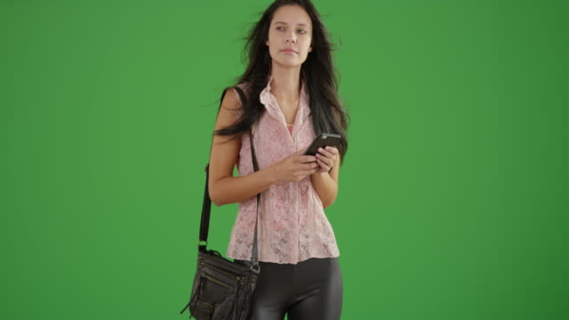 young white girl uses her phone while waiting on green screen - bluse stock-videos und b-roll-filmmaterial