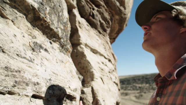Young White Male Rock Climber Looks at a Rock Wall