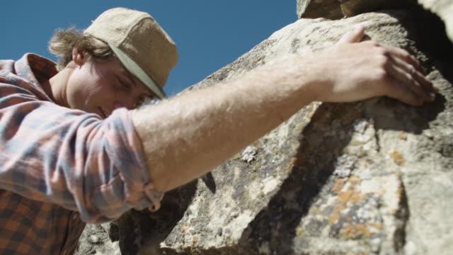 vidéos et rushes de blanc male rock climber échelles un rocher - boulder rock