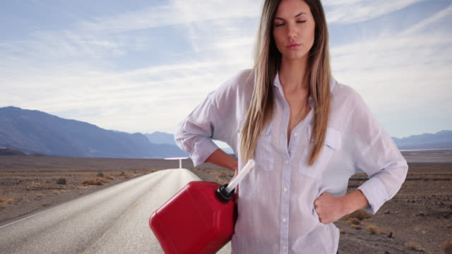 young white woman in need of petrol looking at camera outside on desert highway - petrol tank stock videos and b-roll footage