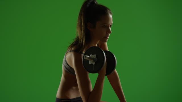 vídeos y material grabado en eventos de stock de young white woman works out while sitting down on green screen - brazo humano