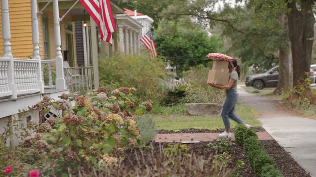 vidéos et rushes de a young wife carrying moving boxes into her new house - carrying