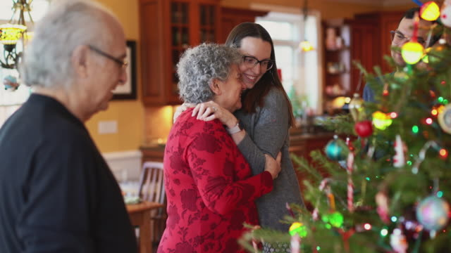 young woman, a daughter, showing her love - hugging and kissing her senior mother, when the big two-generation family decorating a christmas tree in christmas eve - decorating the christmas tree stock videos & royalty-free footage