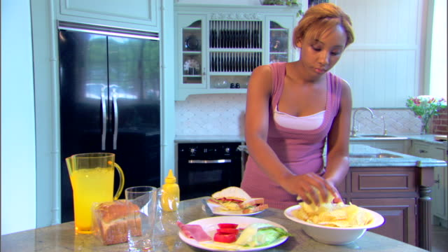 a young woman adds potato chips to her plate and pours a glass of lemonade. - salty snack stock videos & royalty-free footage