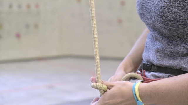 young woman adjusting rock climbing ropes - safety equipment stock videos & royalty-free footage