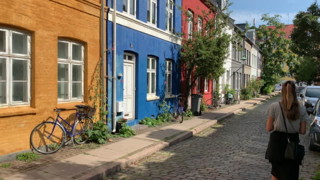 a young woman admires classic colourful buildings in copenhagen - öresundregion stock-videos und b-roll-filmmaterial