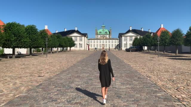 a young woman admires frederiksborg castle, hillerød, denmark - öresundregion stock-videos und b-roll-filmmaterial
